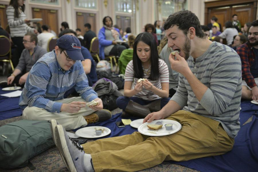 Graduate student John Bonino (right), part of the lower class during Pitt Pantry's Hunger Simulation, is alloted half a bagel for dinner to simulate the issues of poverty and food insecurities in society. Meghan Sunners | Visual Editor