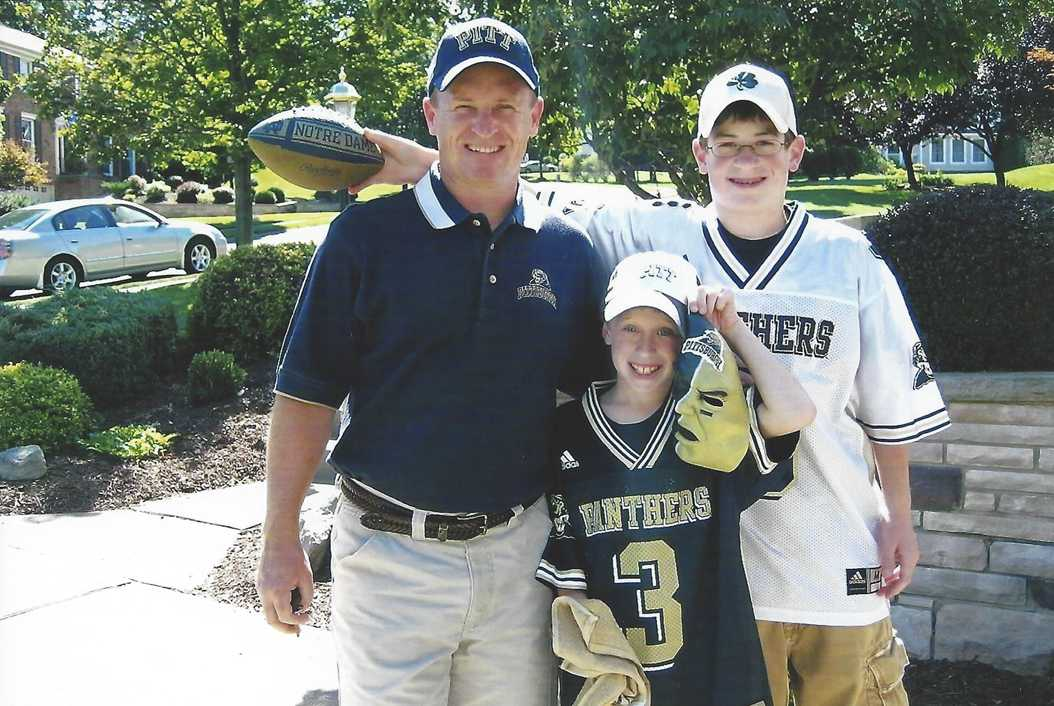 Ryan Zimba (center) pictured with his father and brother outside their home before a Pitt football game in 2007. Courtesy of Ryan Zimba