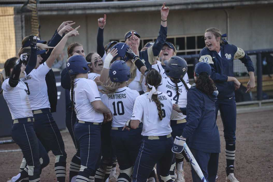 The Pitt softball team greets sophomore Gabrielle Fredericks at home plate after her pinch-hit two-run home run in a 7-1 win over Penn State. Kyleen Considine | Staff Photographer