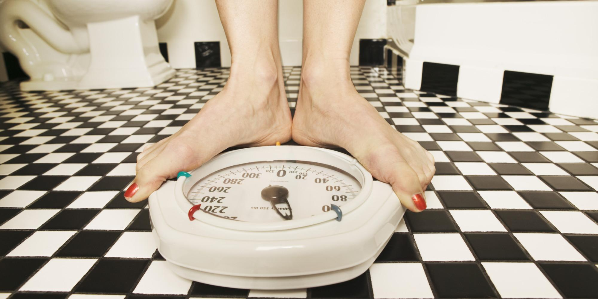 Woman weighing herself on a bathroom scale