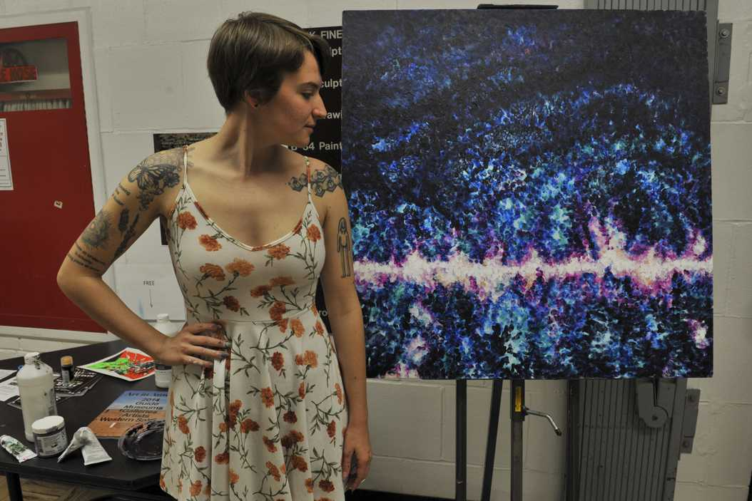 Sarah Thornton, a senior studio arts major, looks at one of her pieces, a
