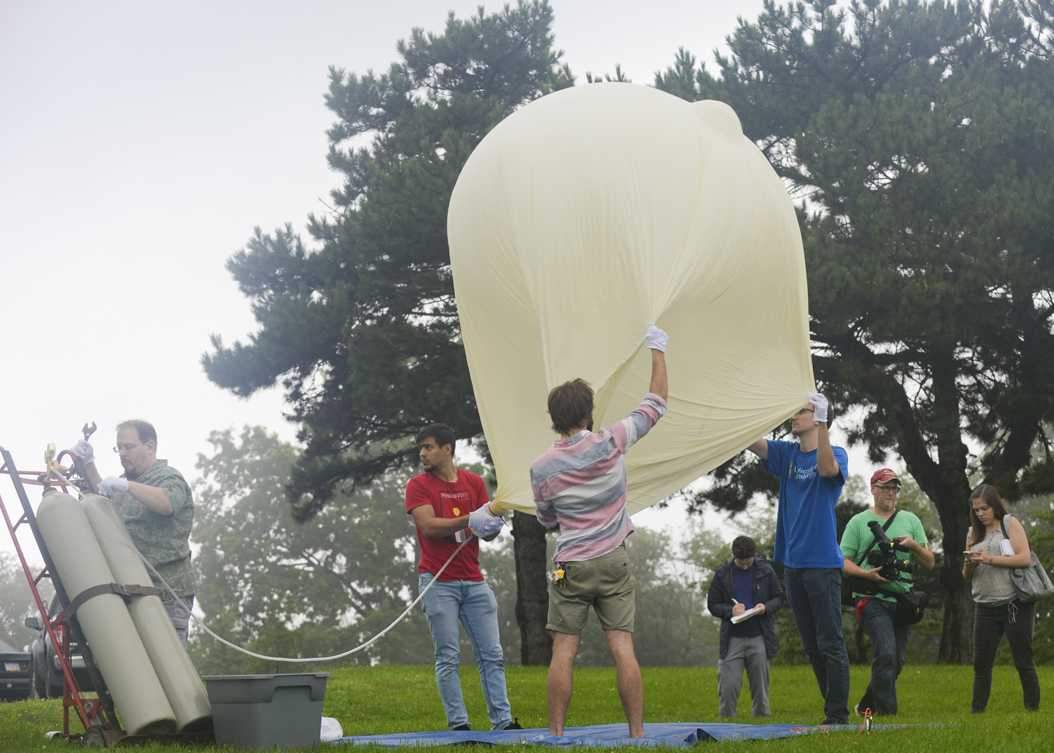 Pitt students hold up the balloon as it is being inflated by Lou Coban, an Electronics Technician at the Allegheny Observatory. (Photo by Anna Bongardino | Visual Editor)