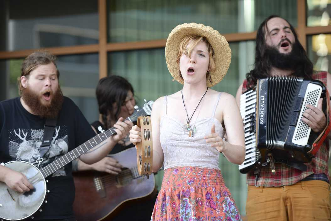 Several members of 4th River Music Collective, a street folk group, perform in front of the Wyndham Hotel at the Three Rivers Arts Festival on Saturday. (Photo by Anna Bongardino | Visual Editor)