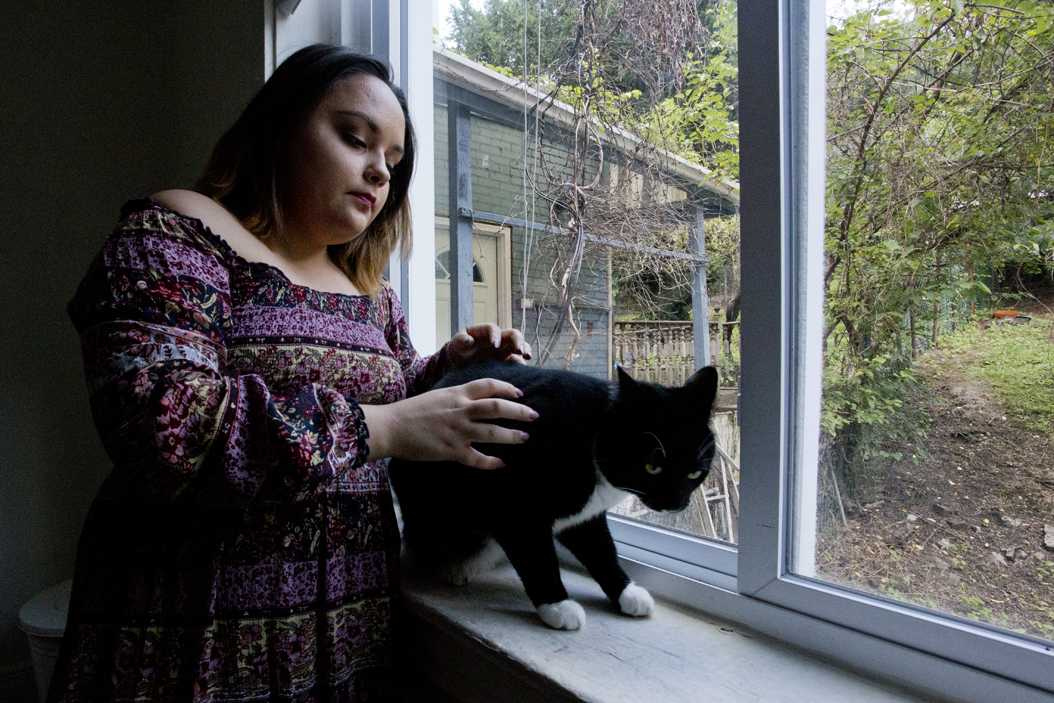 Fifth-year Pitt student Georgia Vidal pets her cat, Winston, on the windowsill of her Bates Street house. (Photo by Jordan Mondell | Contributing Editor)