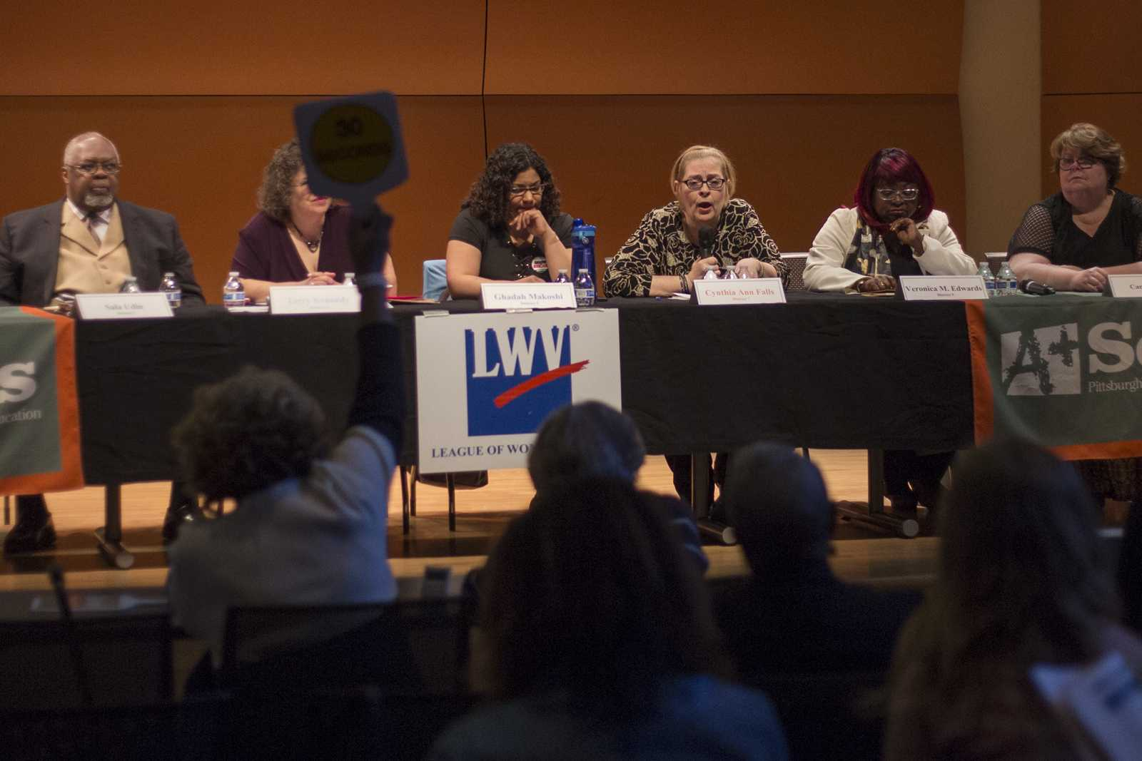 At a school board debate Monday in the Hill District, a moderator holds up a sign, alerting a candidate that they have one minute left to answer. John Hamilton | Editor-in-Chief