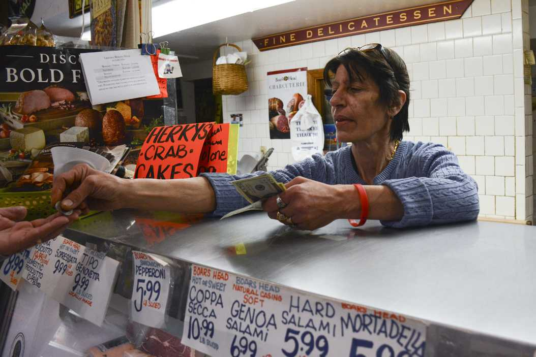 Co-owner of Groceria Merante, Filomena Merante, interacts with a customer over the deli counter in March. She says the store thrives in the summer, even with less students around. (TPN File Photo)