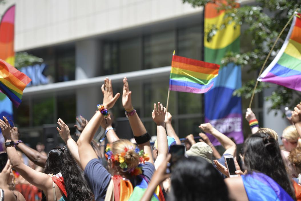 A large group of marchers parade through downtown donning pride flags and rainbow apparel. (Photo by Anna Bongardino | Visual Editor)