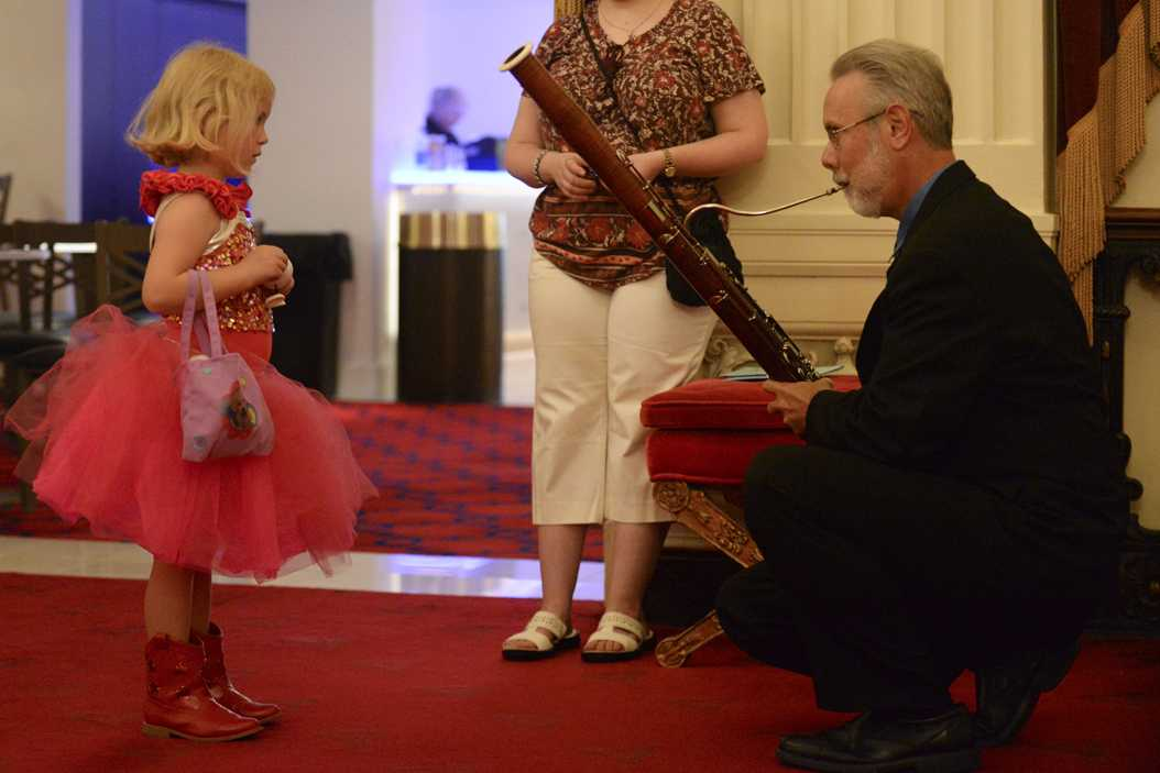 James Rodgers, a contrabassoonist for the Pittsburgh Symphony Orchestra, shows a child how his instrument is played in the Grand Tier Foyer of Heinz Hall before the sensory-friendly performance on Saturday. (Photo by Anna Bongardino | Visual Editor)