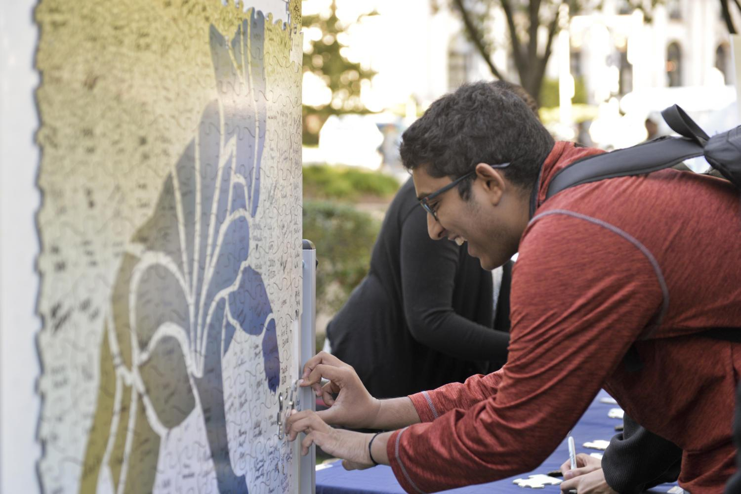 A student adds his name to a panther mosaic at a Year of Diversity event in October 2016. (Photo by Kyleen Considine | Senior Staff Photographer)