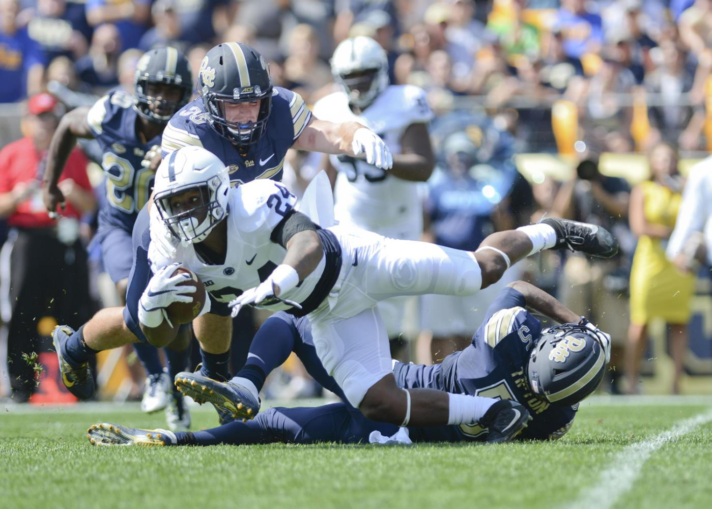 Pitt's Tre Tipton (5) and George Aston (35) tackle Nittany Lions running back Miles Sanders during the Panthers' 42-39 win last season. (Photo by John Hamilton | Managing Editor)