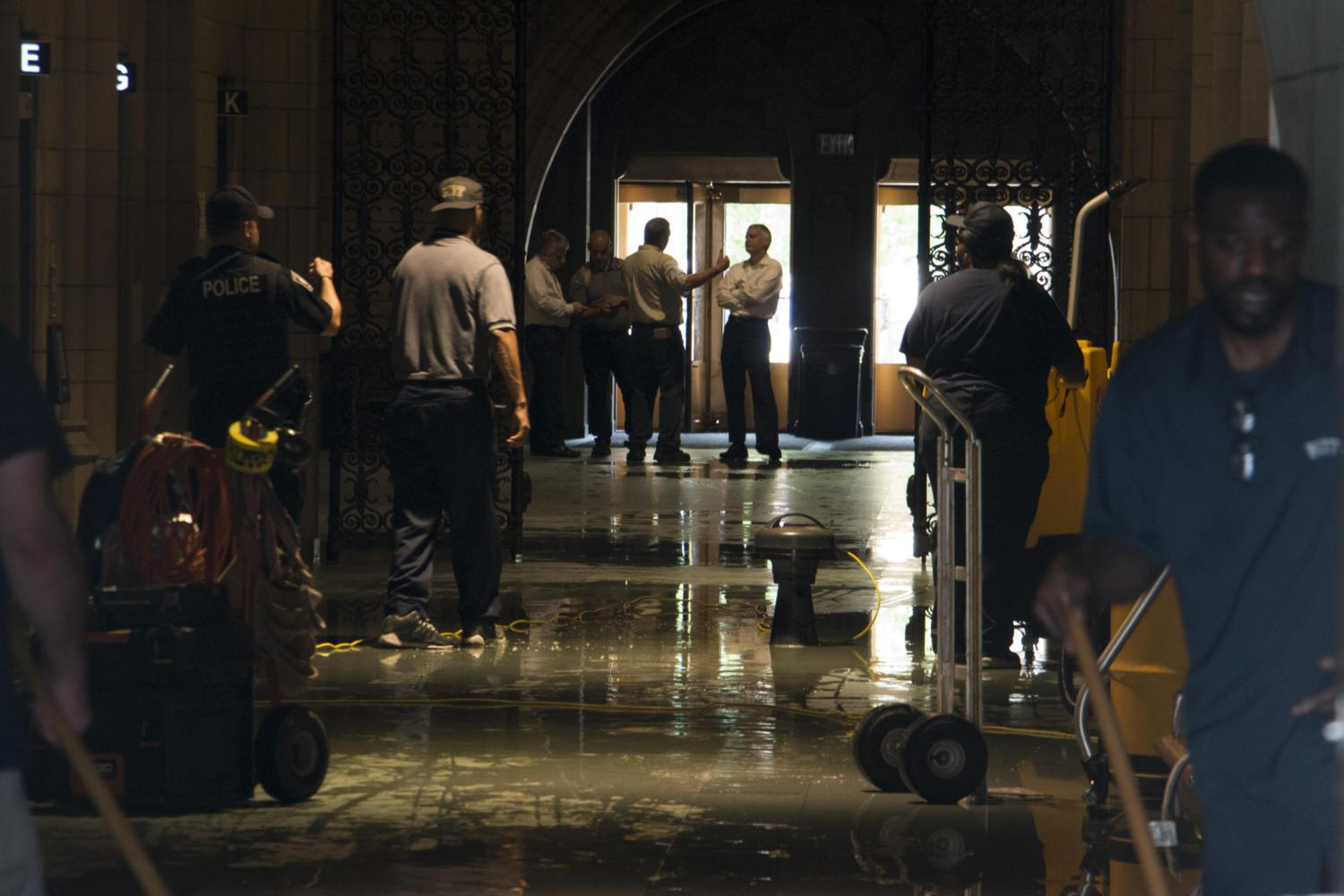 Workers begin to clean up the Cathedral of Learning after a water main broke on the third floor Monday morning. (Photo by John Hamilton / Managing Editor)