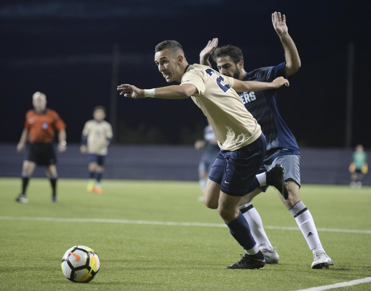 Senior defenseman Robby Dambrot fights for the ball in Pitt's 2-0 win over Longwood Friday night. (Photo by Thomas Yang | Staff Photographer)