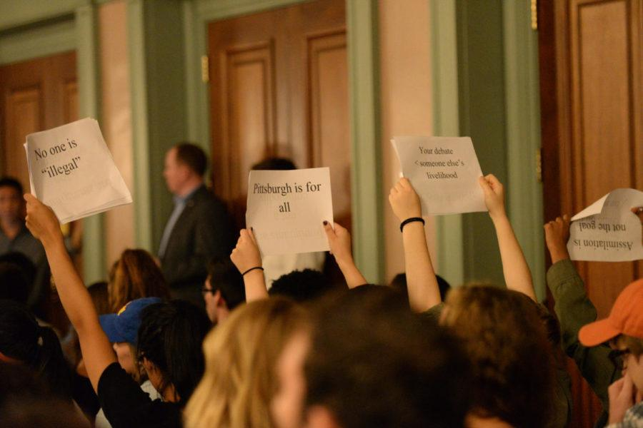 Several students hold signs in protest of the debate between the Cato Institute and the Heritage Foundation on Wednesday night. (Photo by Anna Bongardino | Assistant Visual Editor)