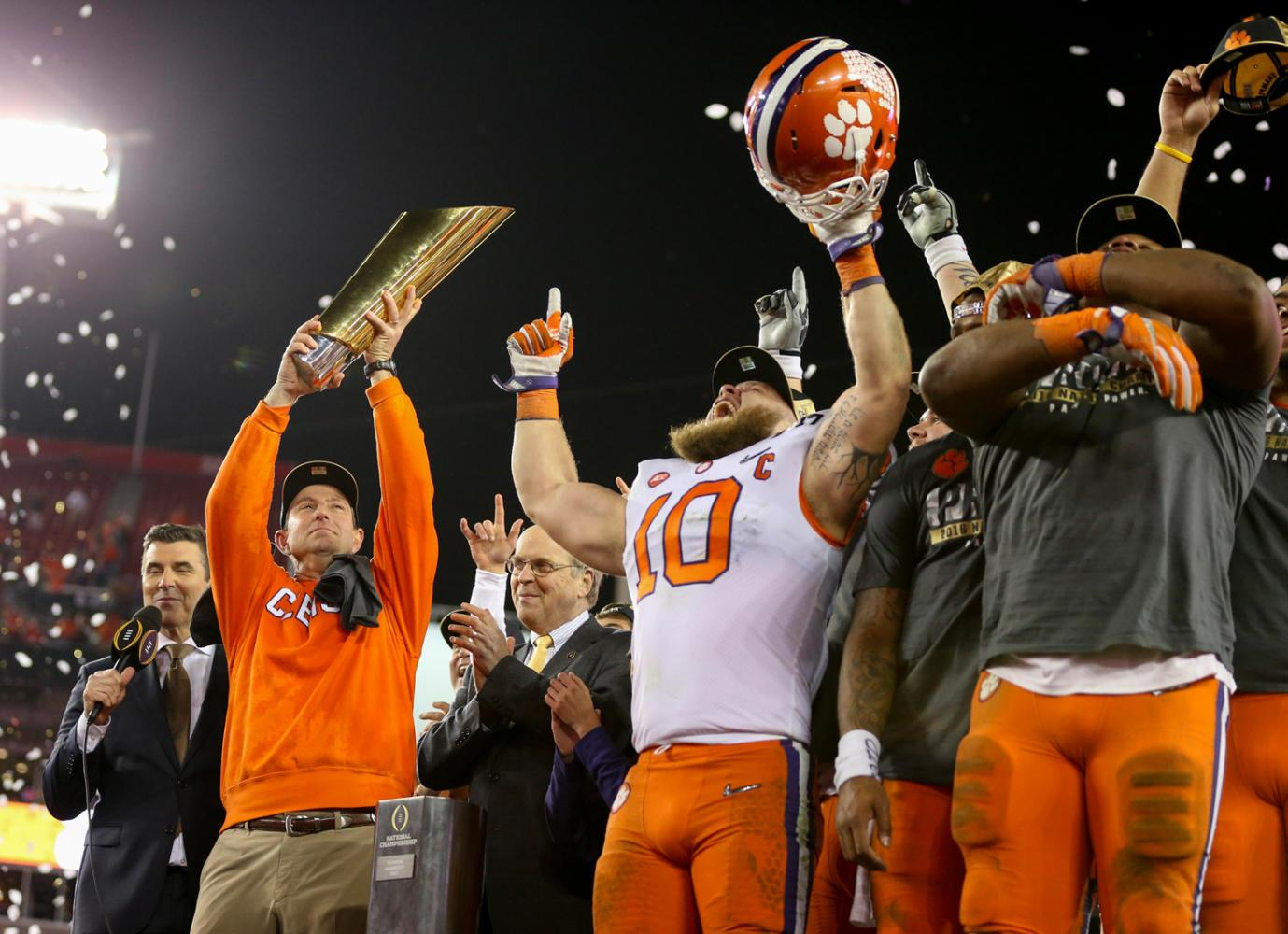 Clemson Tigers head coach Dabo Swinney, left, holds the College Football Playoff National Championship trophy while he and his team celebrate their 35-31 win over the Alabama Crimson Tide Monday, Jan. 9, 2017 in Tampa, Fla. (Loren Elliot/Tampa Bay Times/TNS)