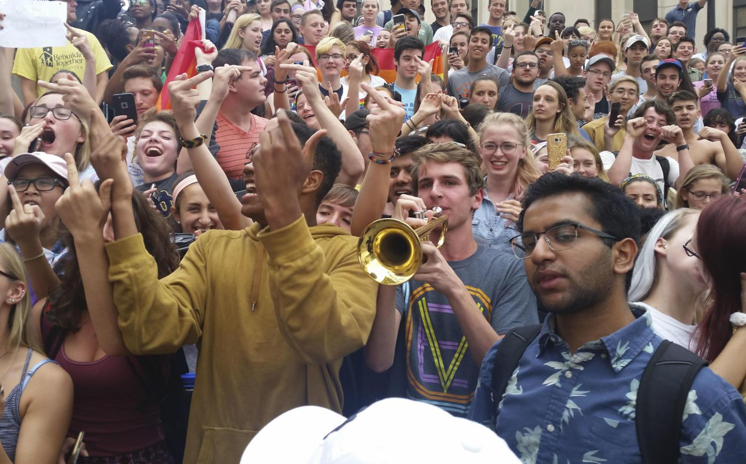 Counter-protestesters sing the Star-Spangled Banner while one student plays along on the trumpet. (Photo by John Hamilton | Managing Editor)