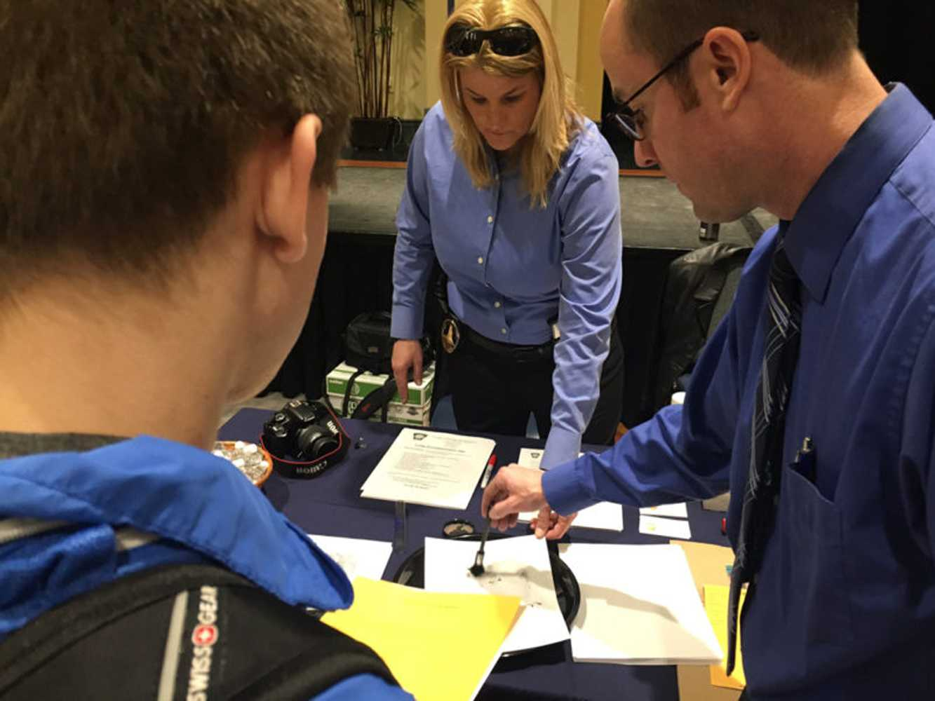 Students watch a fingerprinting demonstration at the Spring Safety Fair in February. (Photo courtesy of DaVaughn Vincent-Bryan)