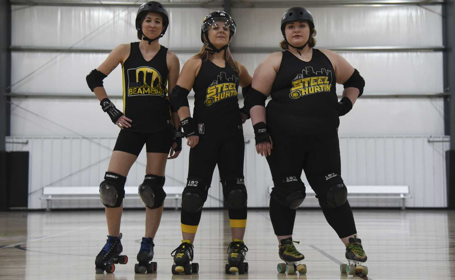 (From left) Alyssa Quintanilla, Jamie Fargo and Alivia Martin stand in the middle of the flat rink at the Pittsburgh Indoor Sports Arena, where they practice and hold games. (Photo by Anna Bongardino | Assistant Visual Editor)