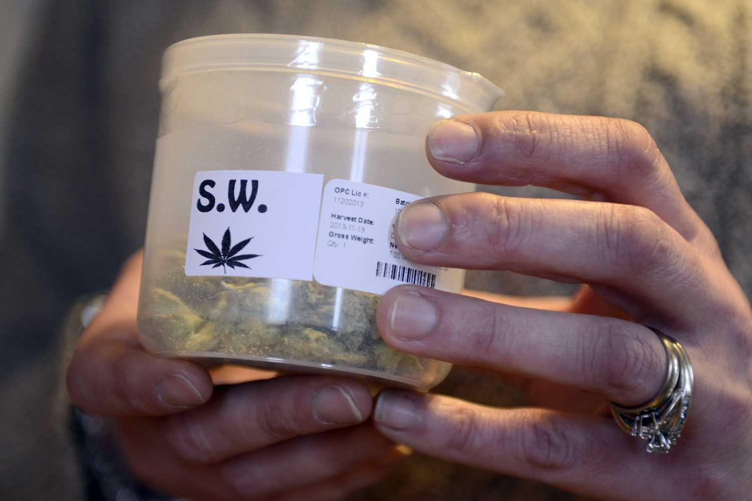 """Tina DeSilvio holds a container of cannabis buds — the """"Sweet Willie"""" strain — she obtained from the Garden State Dispensary. (Tom Gralish/Philadelphia Inquirer/MCTO)"""