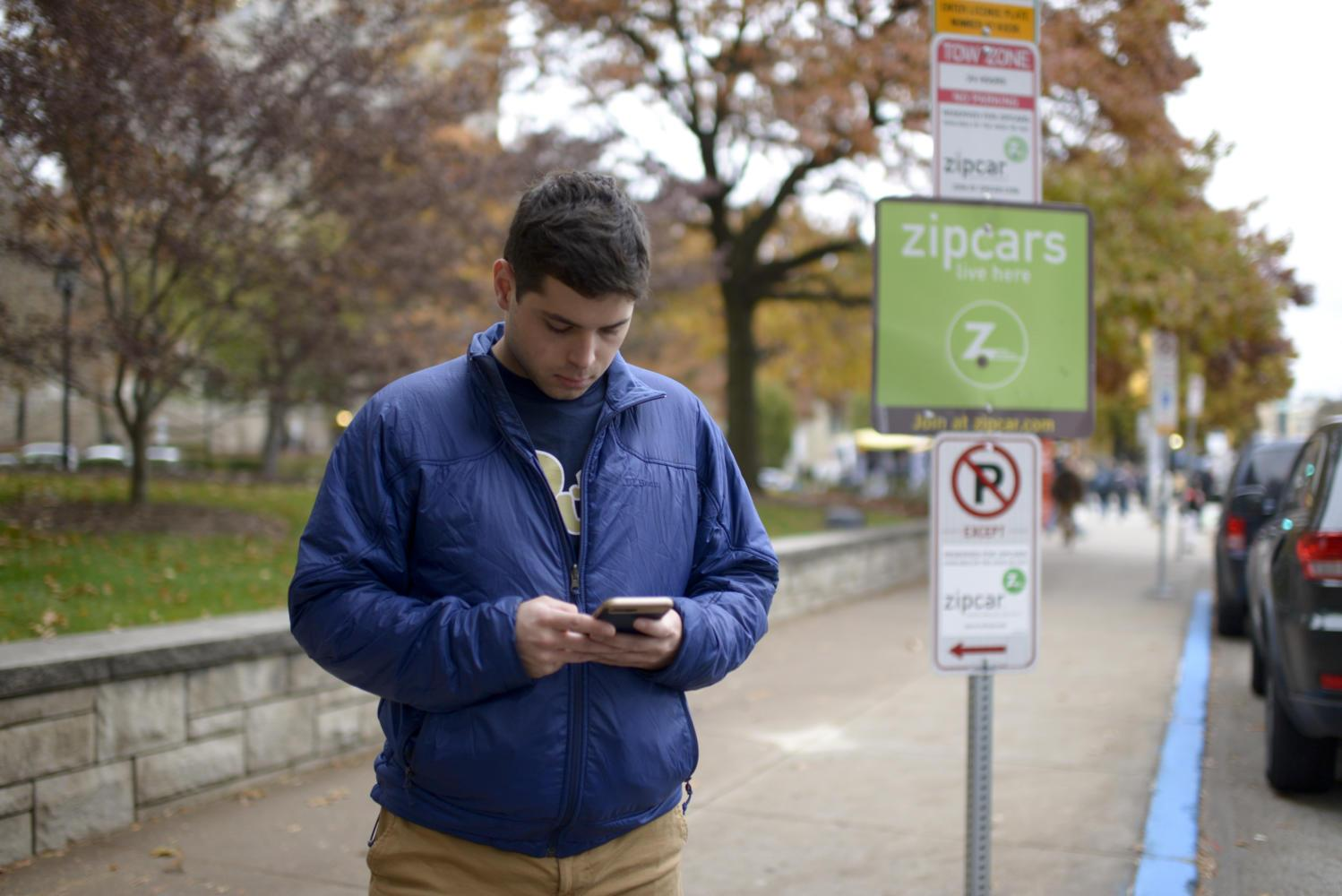 Ian Snyder, a senior political science major, logs into his Zipcar app at the Zipcar spot in front of the William Pitt Union on Forbes Avenue. (Photo by Wenhao Wu | Assistant Visual Editor)
