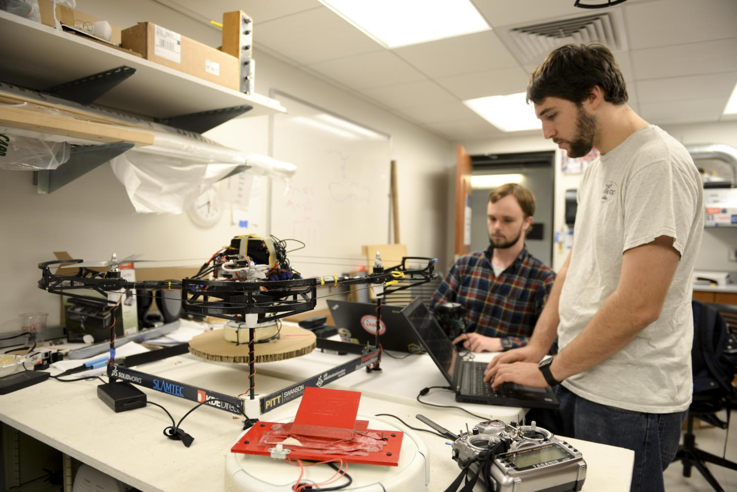 Liam Berti (left) and Levi Burner (right) program the drone in their lab. (Photo by Isabelle Glatts | Staff Photographer)