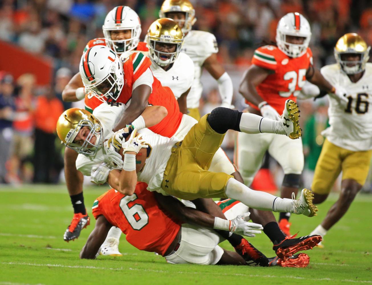 Miami Hurricanes' DeeJay Dallas (13) takes down Notre Dame Fighting Irish wide receiver Chris Finke (10) on a punt return in the first quarter Saturday, Nov. 11, 2017 at Hard Rock Stadium in Miami Gardens, Florida. (Al Diaz/Miami Herald/TNS)