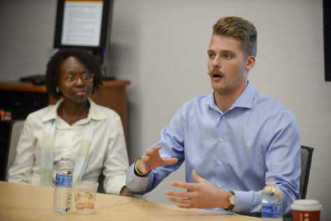 Ian Troost (right), a former Pitt football player, and LaTonya Sharif, athletic director at Holy Family Academy (left), talk during a panel on activism in sports Tuesday in Posvar Hall. (Photo by Aaron Schoen | Staff Photographer)