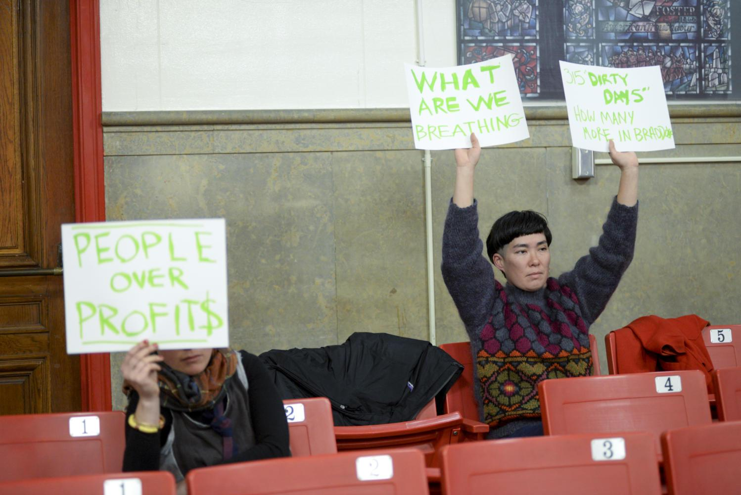 Ginger Brooks Takahashi (right) protested during the Lawrenceville Steel Foundry Public Hearing Monday night at Arsenal Middle School. (Photo by Aaron Schoen | Staff Photographer)