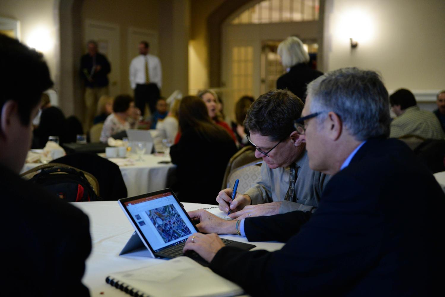 Ron Leibow, an employee of Pitt's Office of Facilities Management, watches on as architect Adam Gross (right) views the campus master plan on his laptop. (Photo by Christian Snyder | Online Visual Editor)