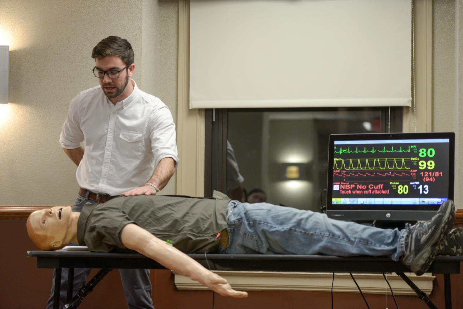 Second-year medical student Paolo Vignali demonstrates routes of administration for Narcan at Pitt Trauma and Emergency League's Narcan Training Tuesday night. (Photo by Sarah Cutshall | Staff Photographer)