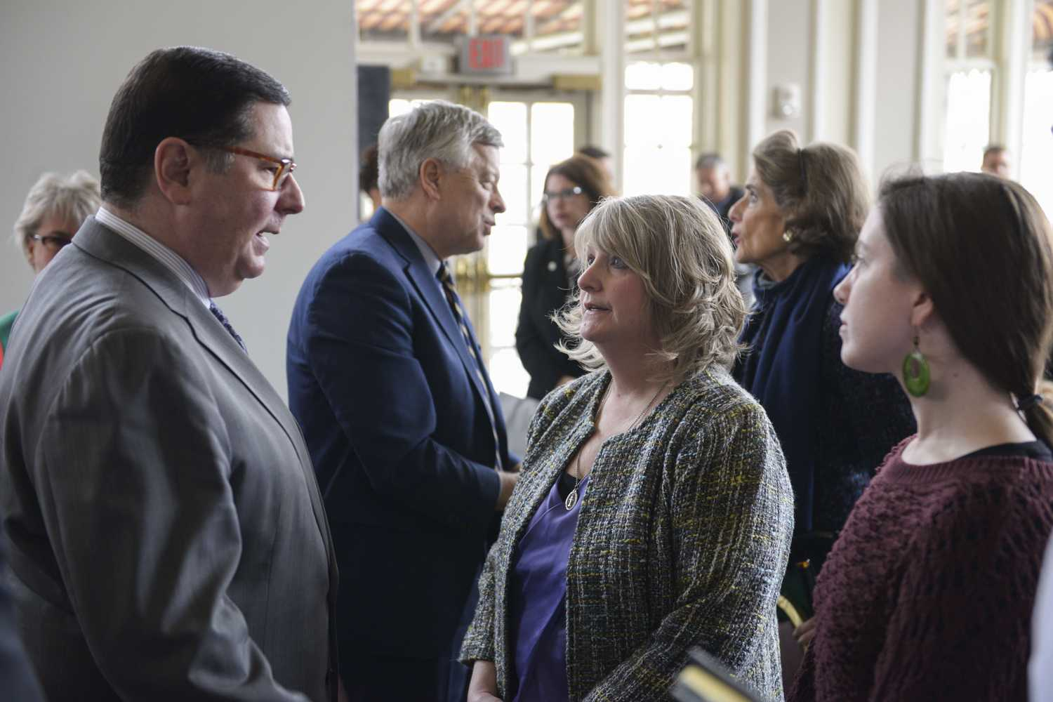 Mayor Bill Peduto (left) speaks with Michelle Lynam and her daughter Kimberly Lawther (right), as former Pitt Chancellor mark Nordenberg greets other guests behind them. (Photo by Chiara Rigaud | Staff Photographer)
