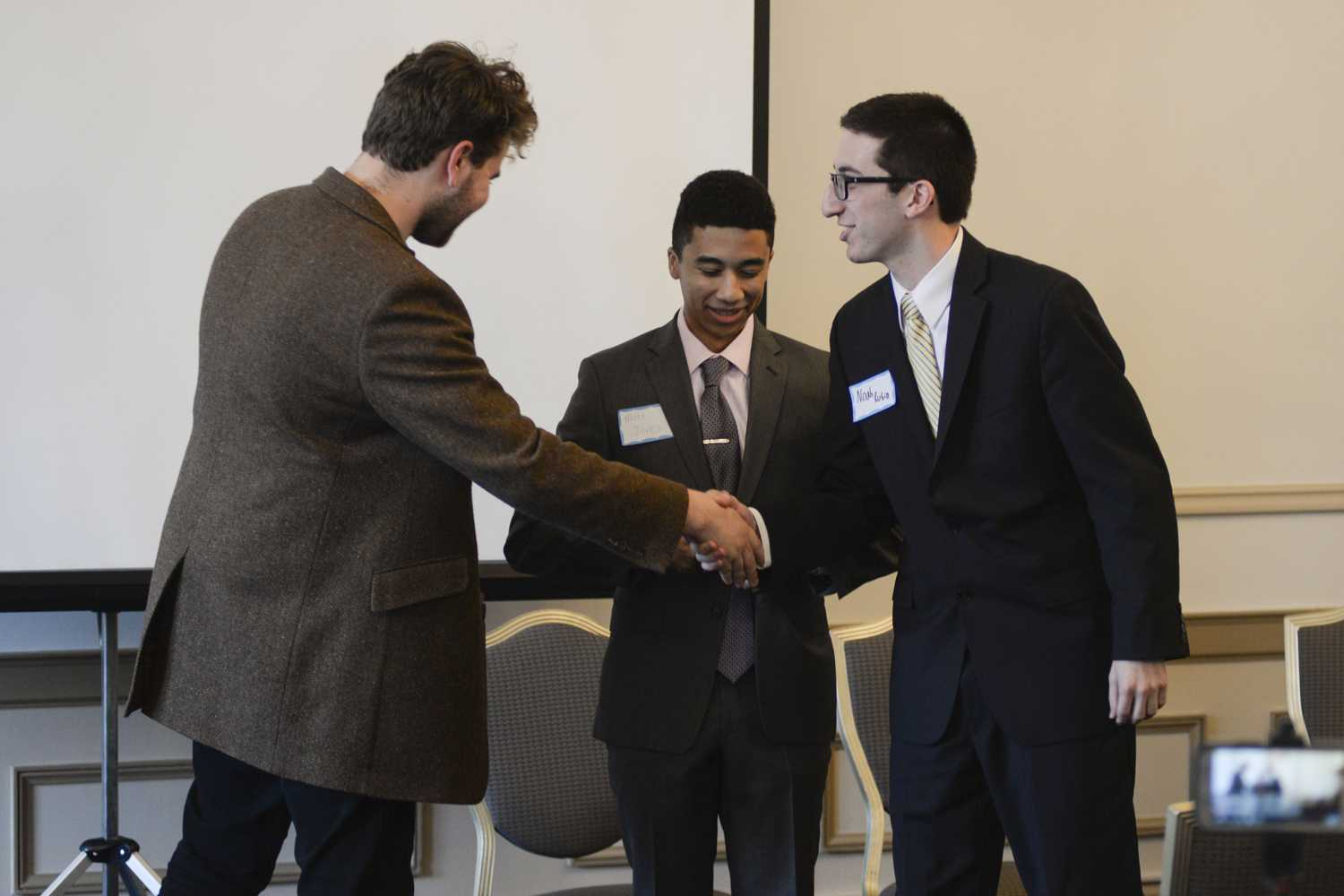Andrew Dow (left), the host of Pitt Tonight, greets candidates Matt Jones and Noah Rubin (right) at the 2018 Meet the Candidates event in the William Pitt Union dining room. (Photo by Sarah Cutshall | Staff Photographer)