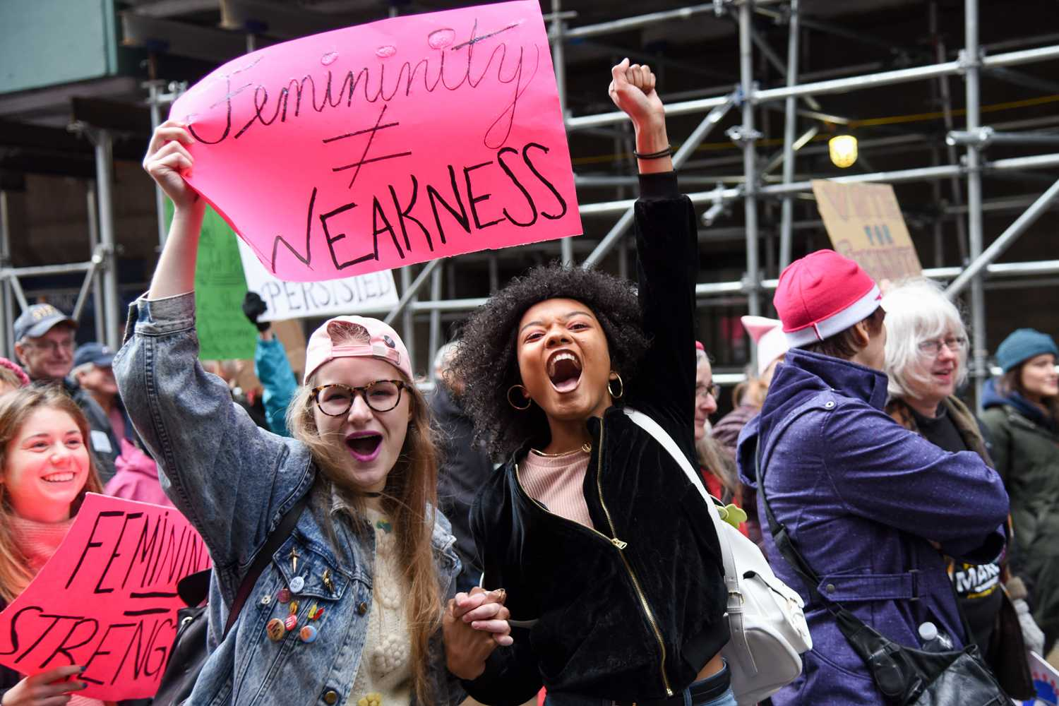 Two marchers cheer while passing through downtown Pittsburgh during Sunday's Women's March. (Photo by Anna Bongardino | Senior Staff Photographer)