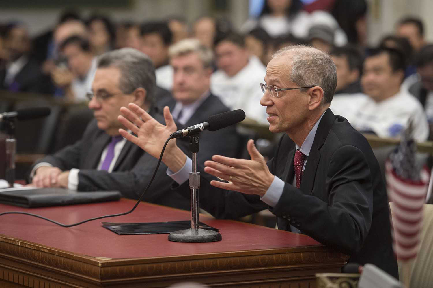 Thomas Farley, MD, health commissioner for the city of Philadelphia, responds to a question from a member of City Council's Committee on Public Health and Human Services during a hearing on a bill that would prohibit beer deli owners from having protective safety glass separating them from their customers during a hearing Dec. 4, 2017. Farley and Dave Perri (left), head of Philadelphia's Department of Licenses and Inspections, support the bill. (Clem Murray/Philadelphia Inquirer/TNS)