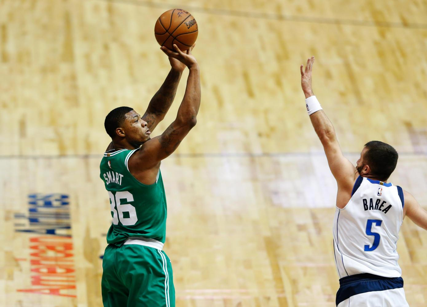 The Boston Celtics' Marcus Smart (36) shoots over the Dallas Mavericks J.J. Barea (5) during the first half at the American Airlines Center in Dallas Nov. 20, 2017. (Vernon Bryant/Dallas Morning News/TNS)