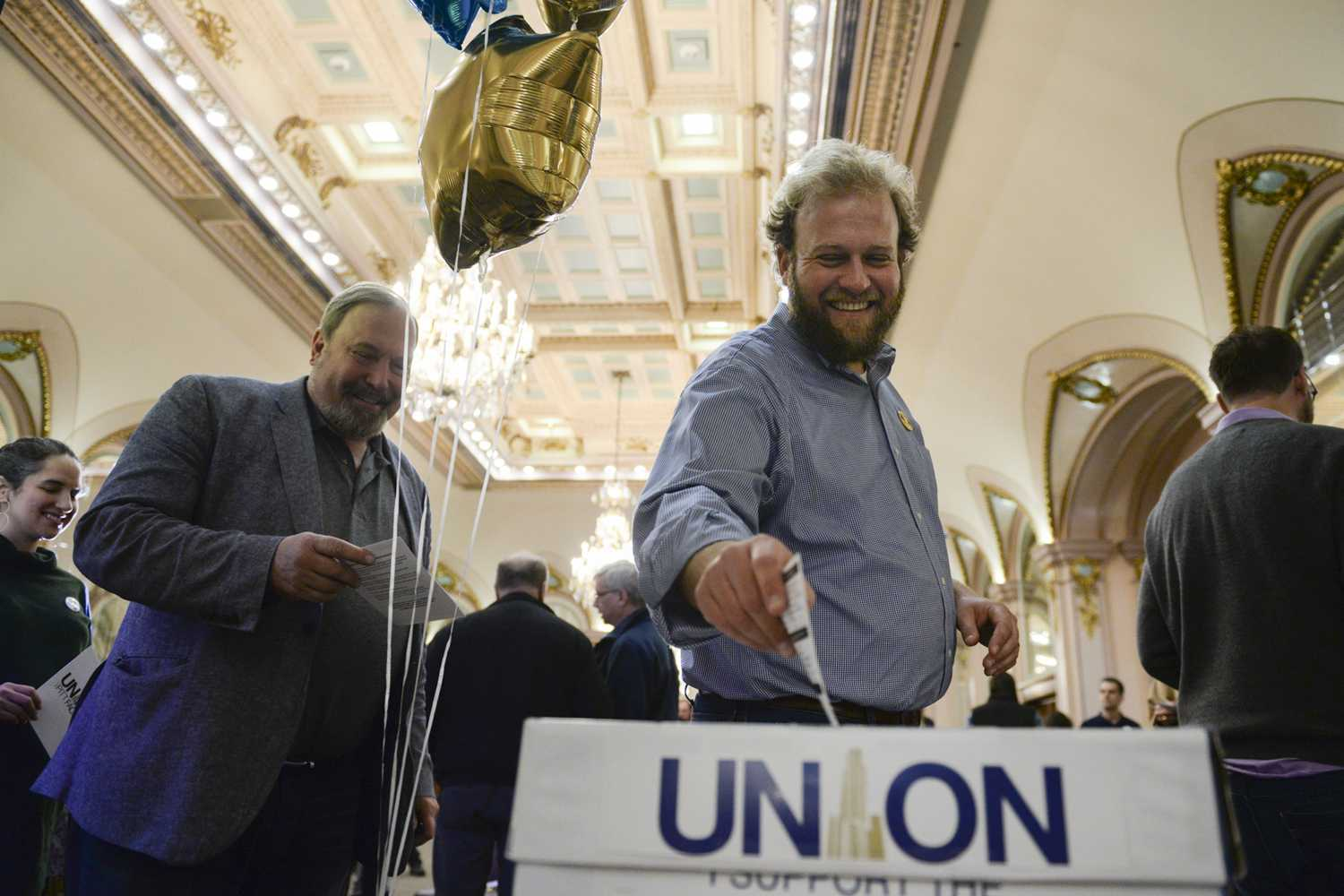 Tyler Bickford, a professor in the English department, drops one of the first union cards at a kick-off event held by Pitt faculty union organizers Monday in the William Pitt Union Ballroom. (Photo by John Hamilton | Contributing Editor)