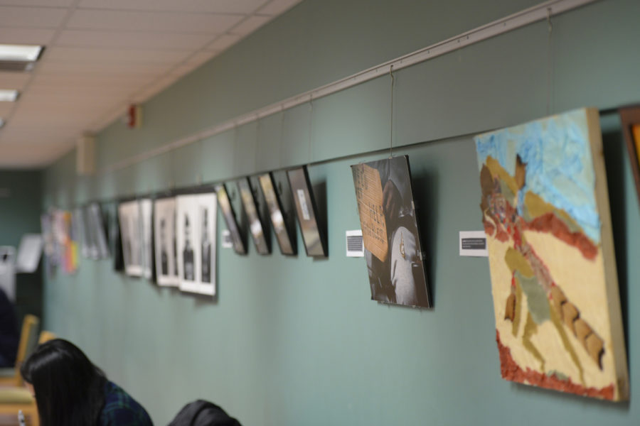 "The exhibit ""Walk On By,"" sponsored by Northside Common Ministries, will hang in the second floor of Scaife Hall until the end of February.  (Photo by Sarah Cutshall 