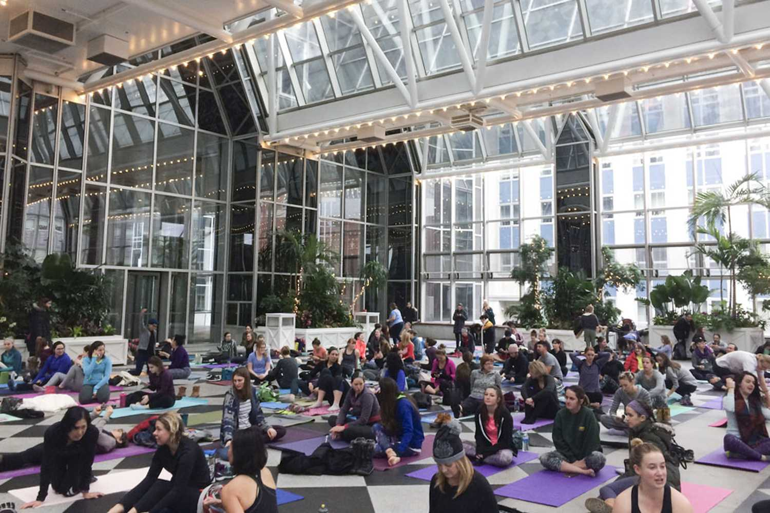 Women and men fill PPG Place's Wintergarden room as Pittsburgh Downtown Partnership and Highwoods Properties host a free, first-time yoga class Sunday morning. (Photo by Sarah Connor | Contributing Writer)
