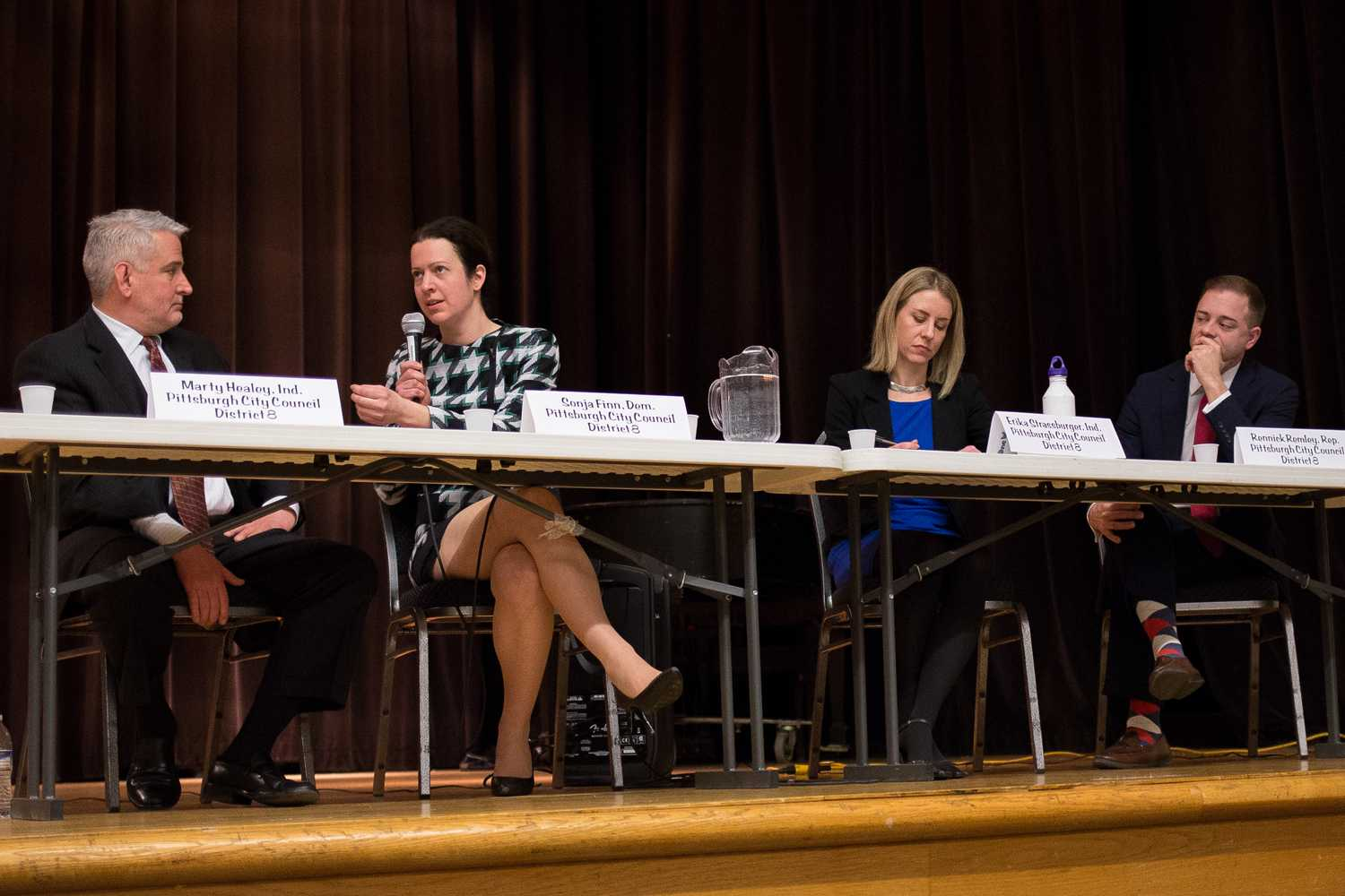 District 8 candidates Marty Healey (far left), Erika Strassburger (right) and Rennick Remley (far right) listen as Democratic candidate Sonja Finn(left) gives her stance on gun violence at Thursday evening's District 8 Special Election Candidates Town Hall. (Photo by Thomas Yang | Visual Editor)