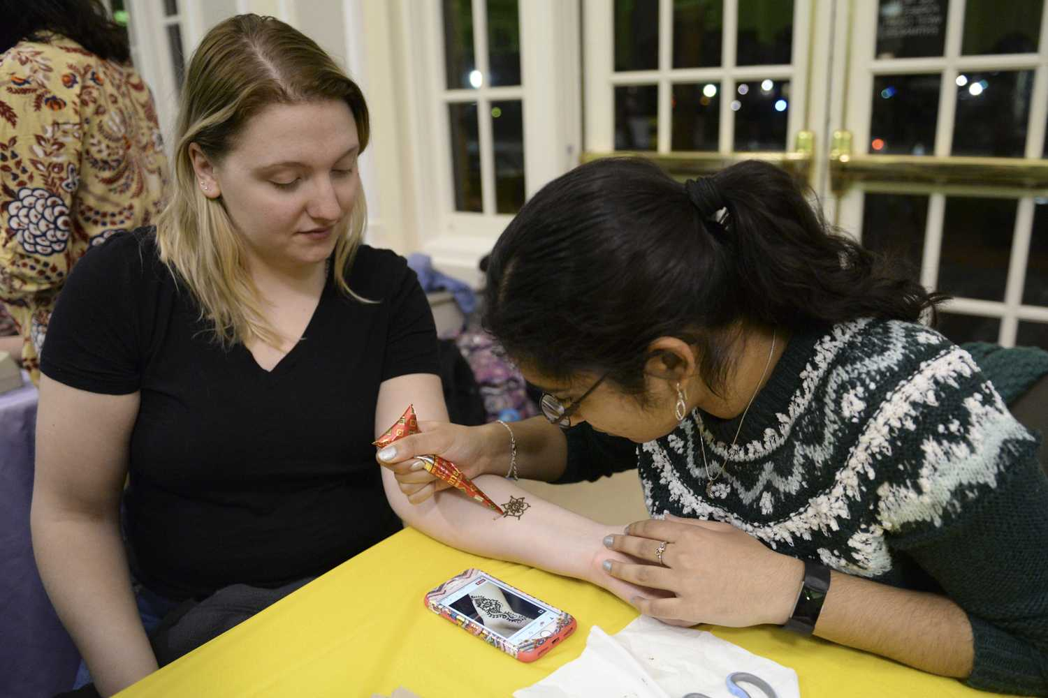 Lauren Kubeja (left), a junior studying civil engineering, receives a henna tattoo from Insiyah Campwala (right), a senior majoring in biology, at the Indian table during the Who Run the World? event Monday night in the William Pitt Union. (Photo by Issi Glatts | Staff Photographer)