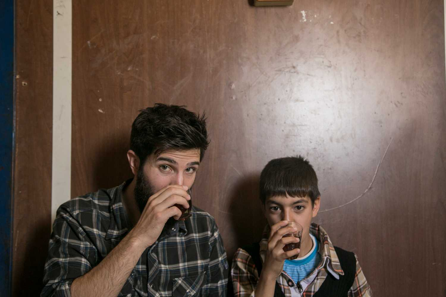 Zach Ingrasci, co-director of Salam Neighbor, shares tea with Raouf, one of the subjects of the documentary. (Image via Wikimedia Commons)
