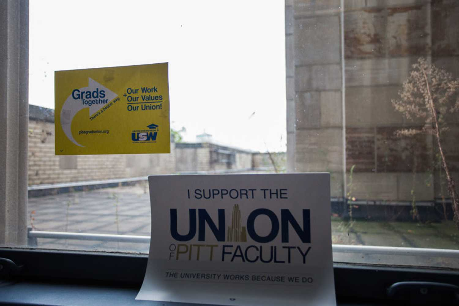 Signs supporting the graduate and faculty unions hang on a window in the Cathedral of Learning. (Photo by John Hamilton | Managing Editor)