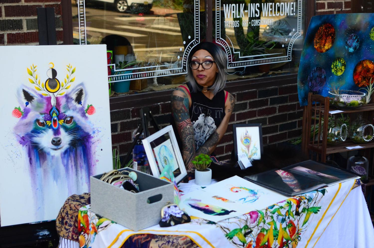 Christan Miller, owner of Eclipse Tattoo in Springdale, sits outside the Ravenwood Collective on Butler Street with her artwork on display at the 2018 Lawrenceville Art Crawl. (Photo by Jon Kunitsky | Staff Writer)