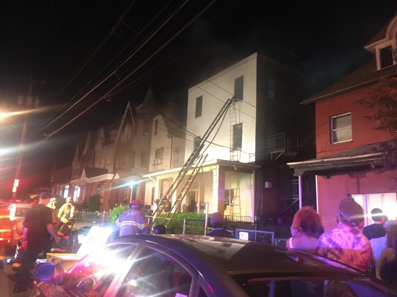 Firefighters enter the second story of an apartment building at 3315 Ward Street after a three-alarm fire struck the building. (Photo by Hannah Schneider | Contributing Editor)