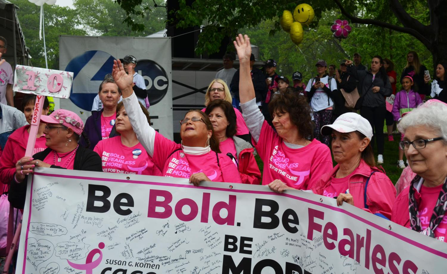 "A group of women at the 2018 Komen Pittsburgh Race for the Cure show their support holding a banner stating the event's motto, ""Be Bold. Be  Fearless. Be More Than Pink."" (Photo by Jon Kunitsky 