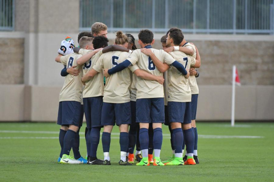 Players of the Pitt men's soccer team huddle together on the field during a game. (Photo courtesy of Pitt Athletics)