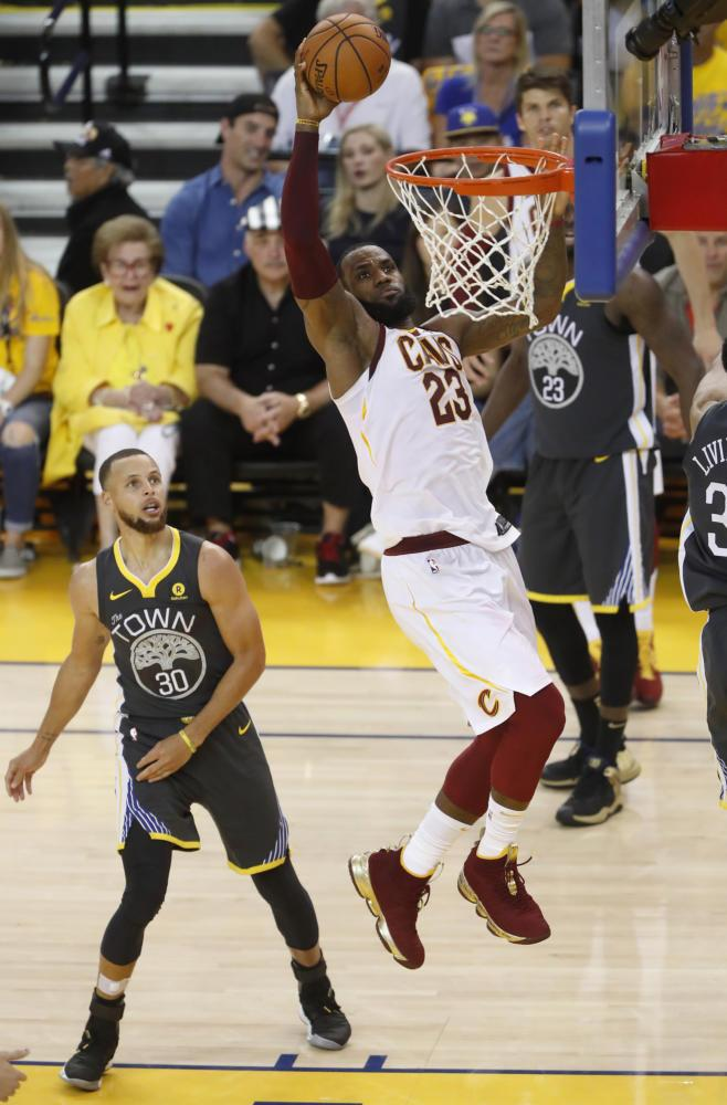 Cleveland Cavaliers' LeBron James (23) dunks against Golden State Warriors' Stephen Curry (30) in the fourth quarter of Game 2 of the NBA Finals Sunday, June 3, in Oakland, CA. (Nhat V. Meyer/Bay Area News Group/TNS)