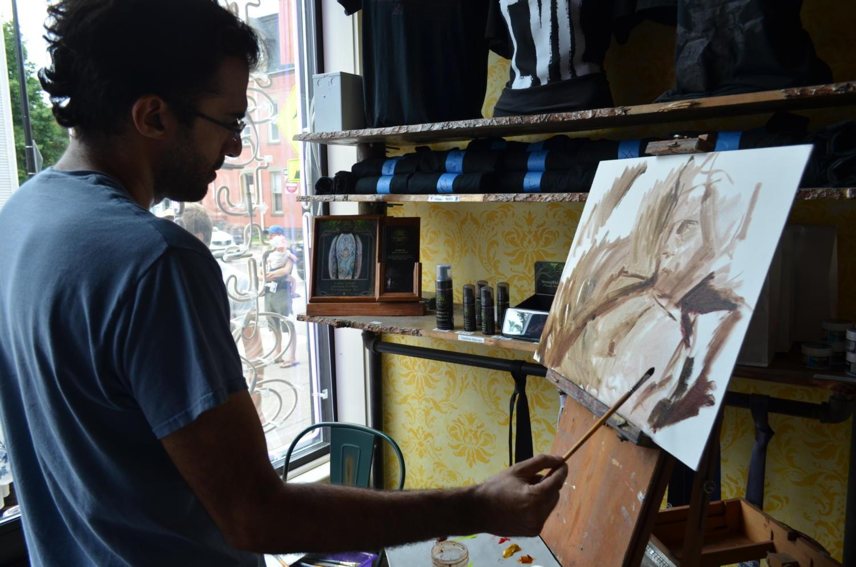 Artist Shervin Iranshahr paints a portrait of Jeff Goldblum as a part of Friday's Jeff Goldblum Day festivities.