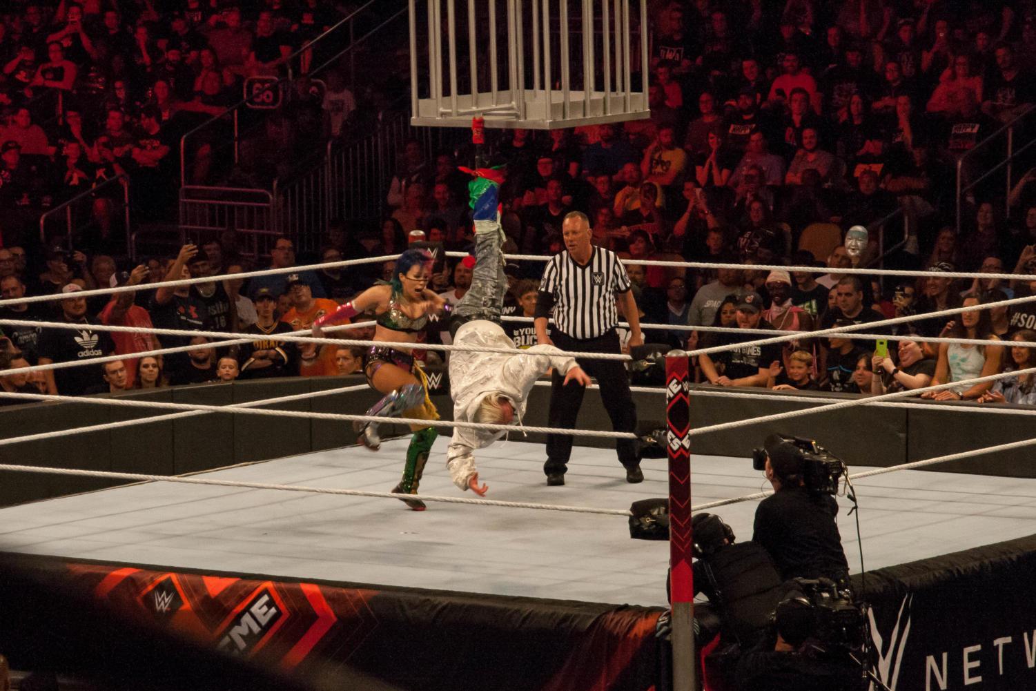 Asuka (left) takes the opportunity for revenge on James Ellsworth after his interference in a previous match.