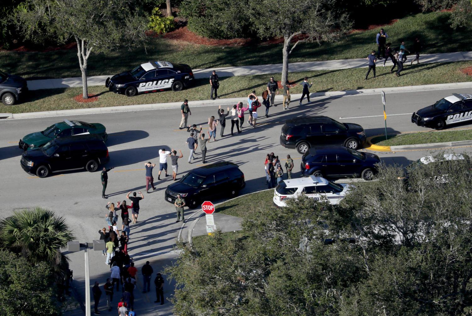 Students are evacuated by police out of Stoneman Douglas High School in Parkland, Fla., after a shooting on February 14, 2018. (Mike Stocker/Sun Sentinel/TNS)