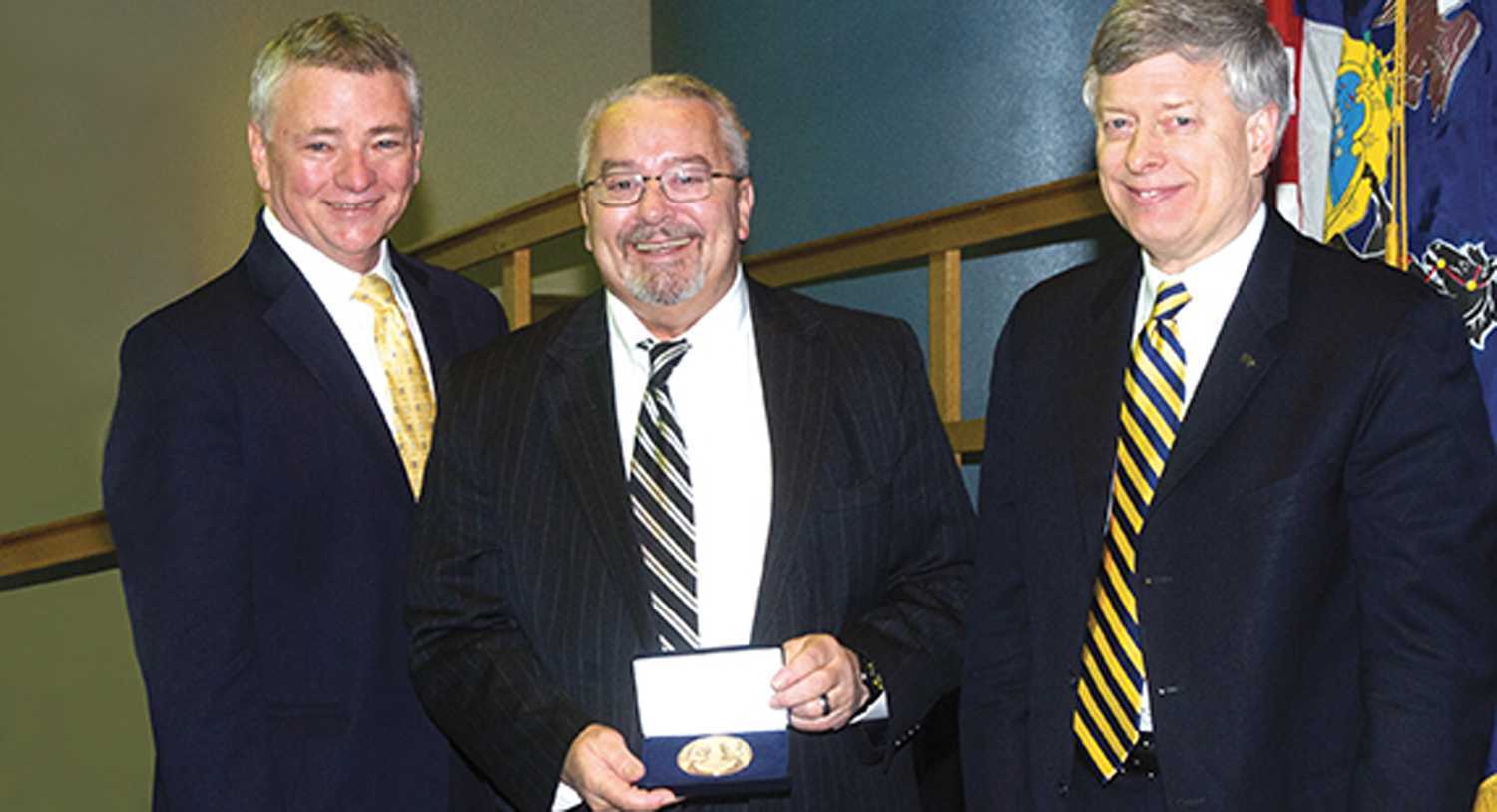 Jerome Cochran (center) was awarded Pitt's 225th Anniversary Medallion in February 2013 at a Board of Trustees meeting. (Photo via PittChronicle)